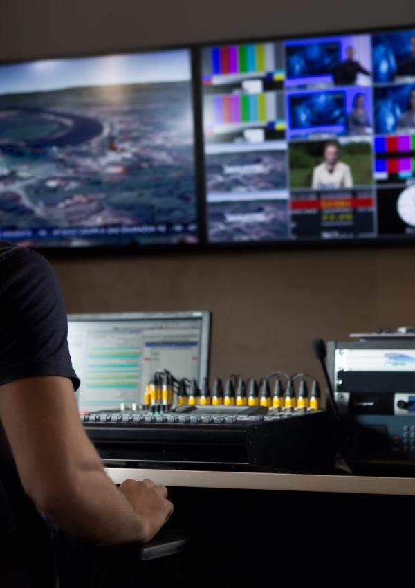 Homem sentado em frente a monitores de edição de um programa de TV