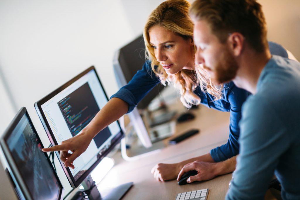 Em uma sala com vários computadores, uma mulher e um homem da Ciência da Computação analisam uma tela