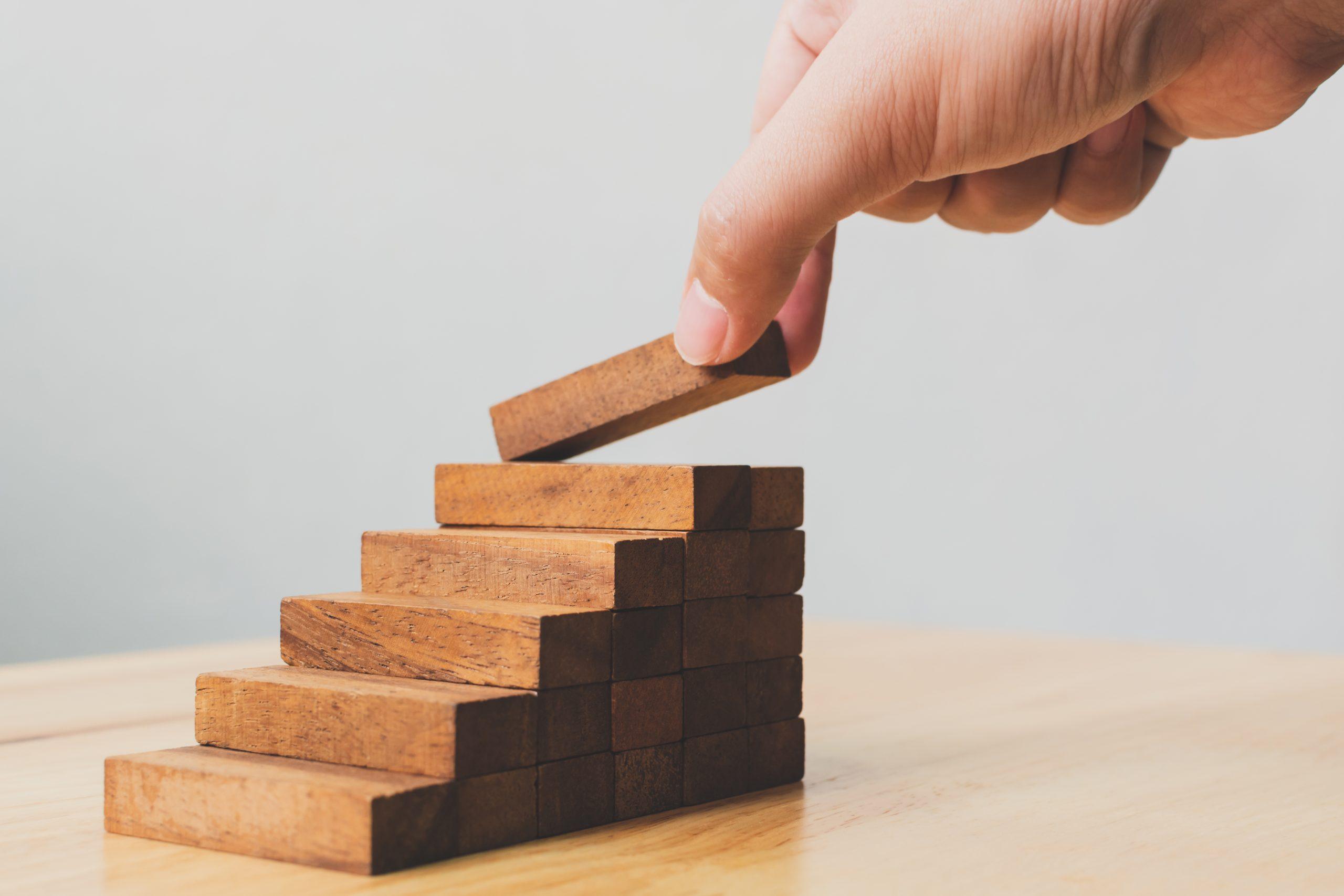 Conceitos MEC - Imagem mostra uma mão colocando o último degrau de uma escada por meio de brinquedo de montar