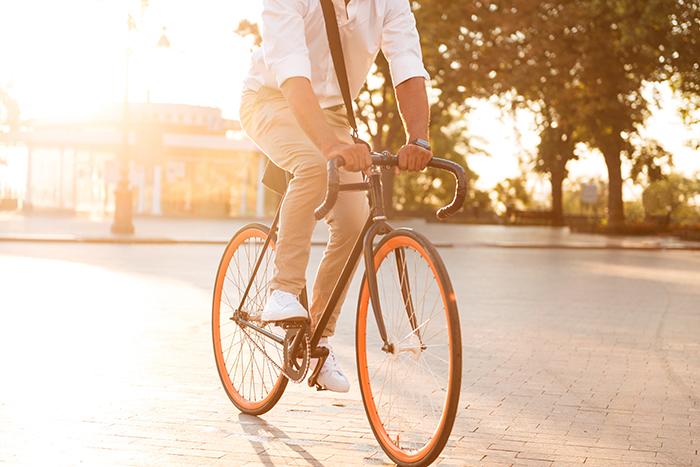 Homem com roupa social se locomovendo de bicicleta na rua
