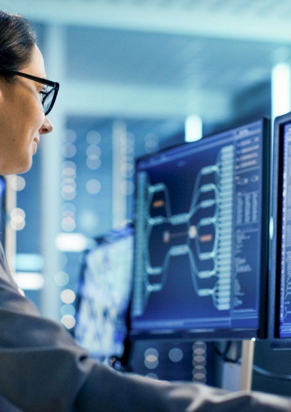 Jovem sentada em frente ao computador e na tela do dispositivo aparece diversos códigos de programação tecnológica