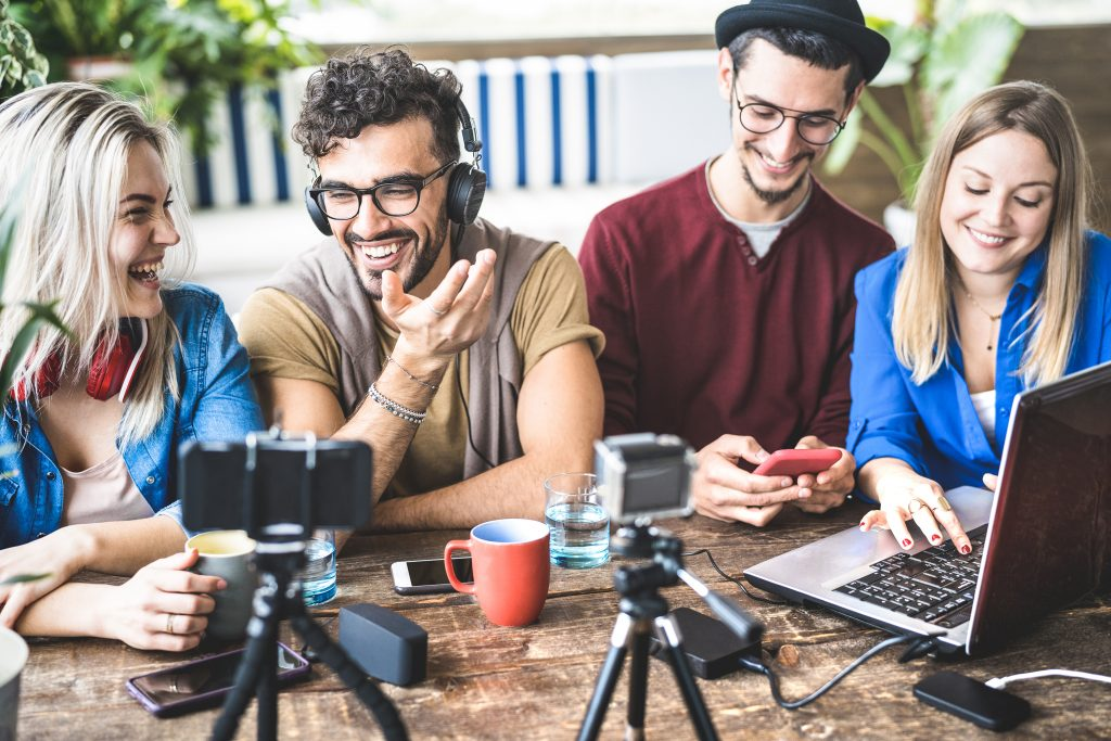 Profissionais de comunicação em uma mesa trabalhando com equipamentos de tecnologia