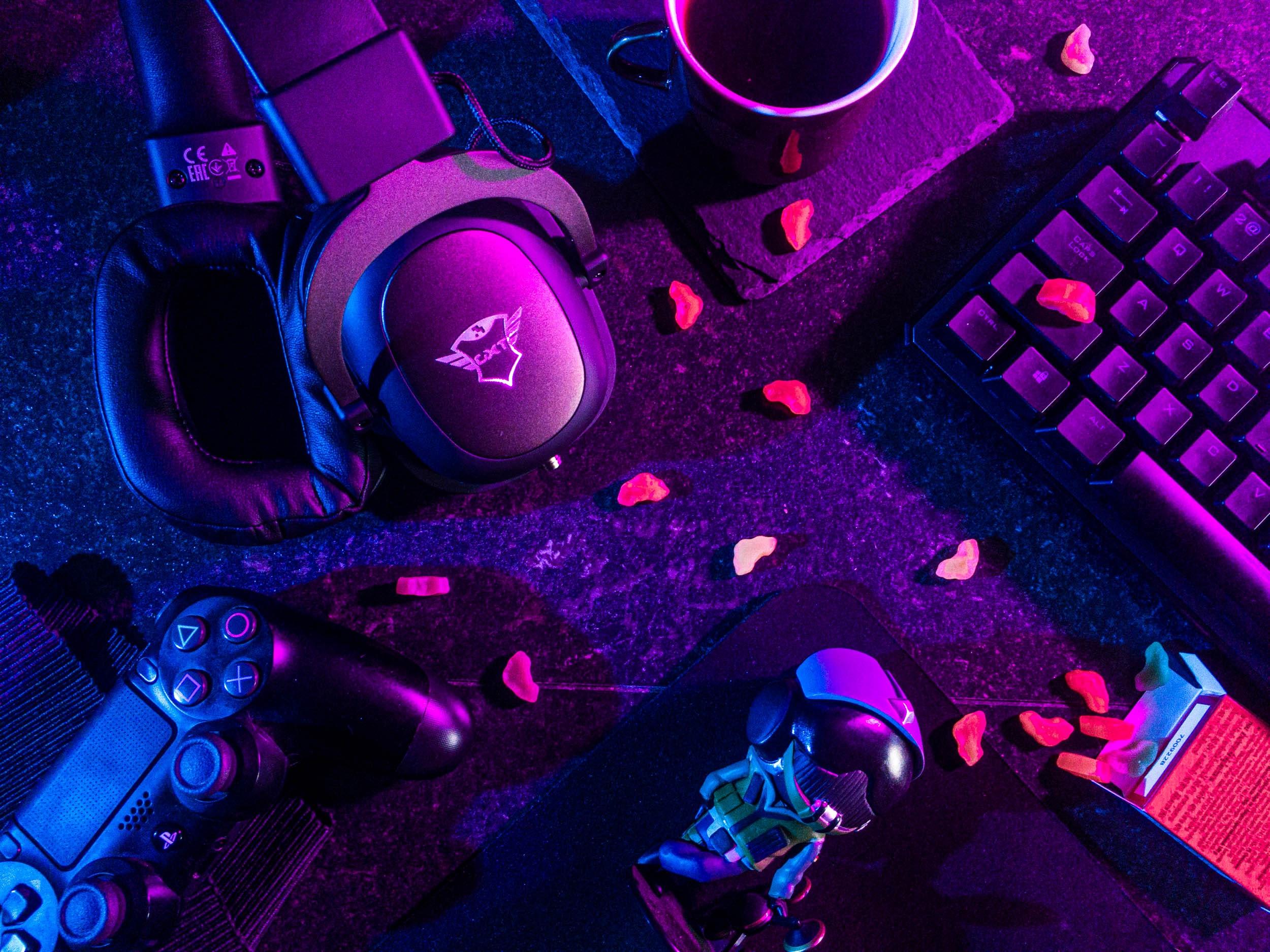 Mesa com alguns objetos ligados aos games: controle remoto, bonequinho, café, drops e teclado de computador