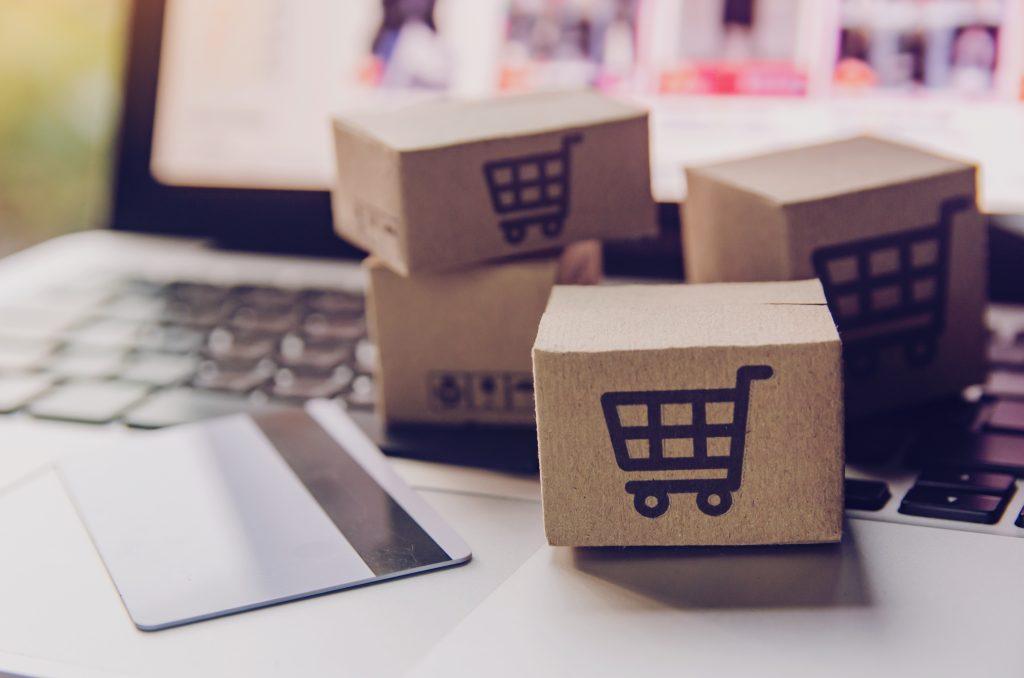 Minicaixas de papelão com desenhos de carrinho de compras sobre um notebook ligado e com um site aberto