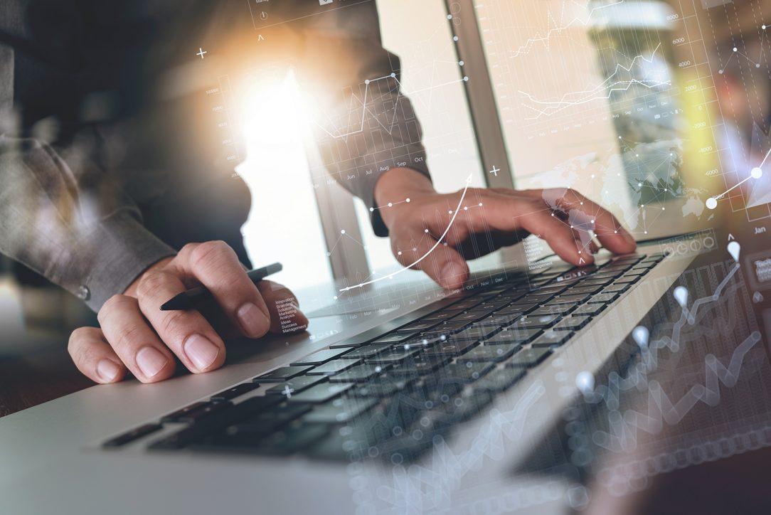 Análise e Desenvolvimento de Sistemas - mãos de um homem com uma caneta entre os dedos e sob o teclado de um computador com vários gráficos sobrepostos à imagem