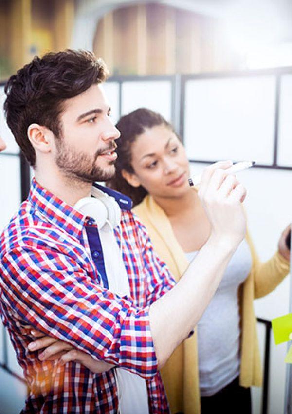 Dois rapazes e uma moça olham para várias ideias durante aula em escola de negócios
