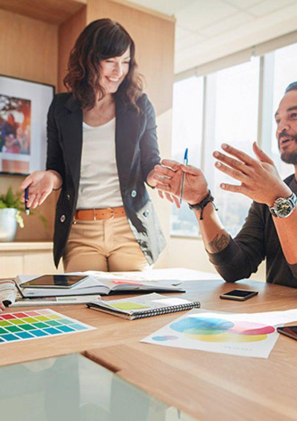 Quatro pessoas trabalham na produção publicitária; dois homens e duas mulheres conversam sobre a mesa cheia de paletas e papeis