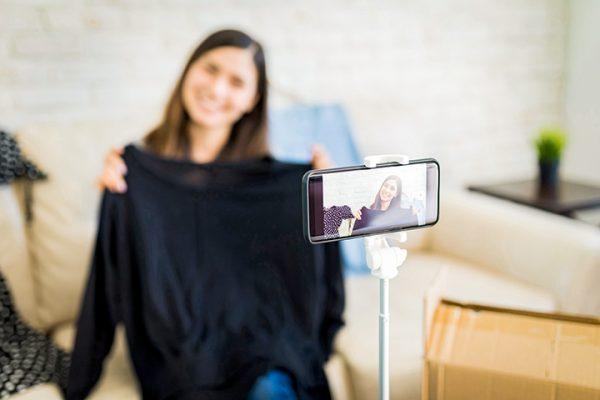 Menina da dicas de vídeo pelo celular mostra blusa preta e grava a cena com celular em primeiro plano