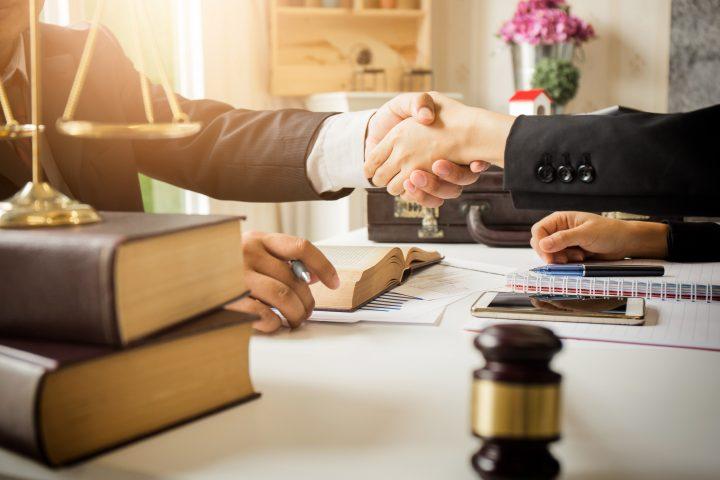 Em um escritório de Direito dois homens se cumprimentam com as mãos sob uma mesa com livros e o martelo que representa a justiça