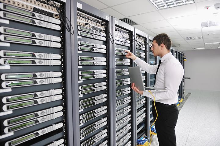 Homem vestido de calça preta e camisa branca trabalha em um servidor com Redes de Computadores