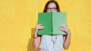 Menina segurando um livro com capa verde no rosto, aparecendo somente os olhos