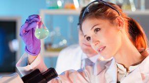 Química é área promissora com mulher segurando um vidro