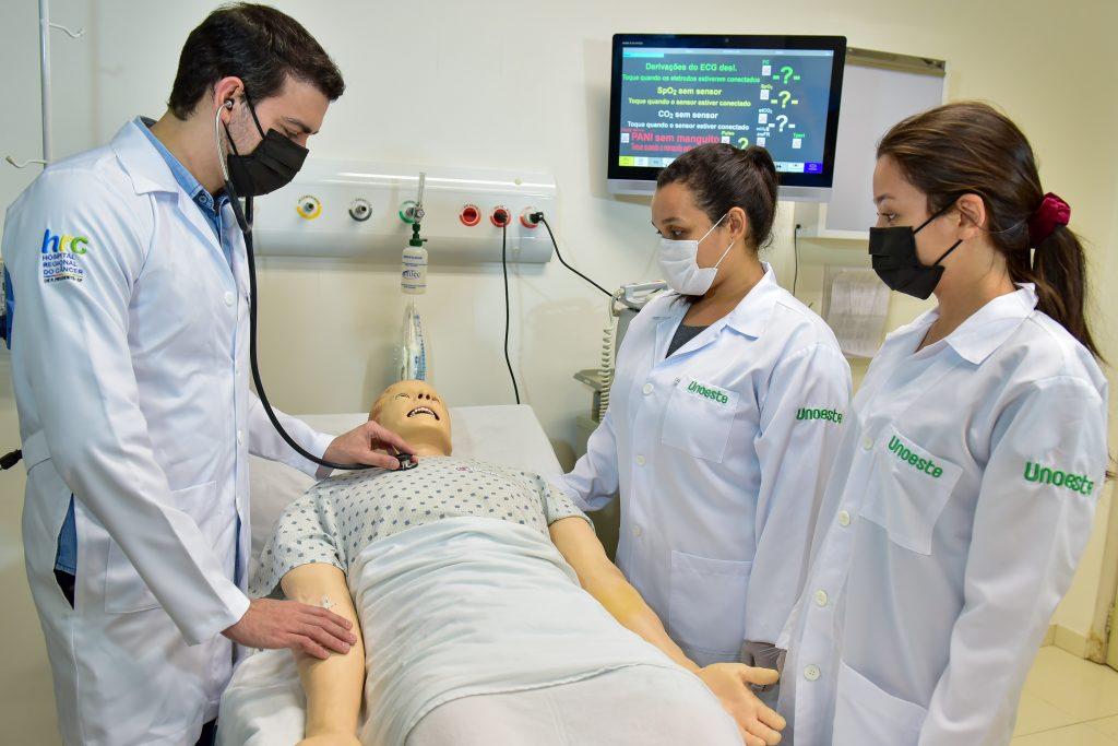Faculdade de Medicina - Professor fazendo auscuta em um robô de simulação e duas alunas observam