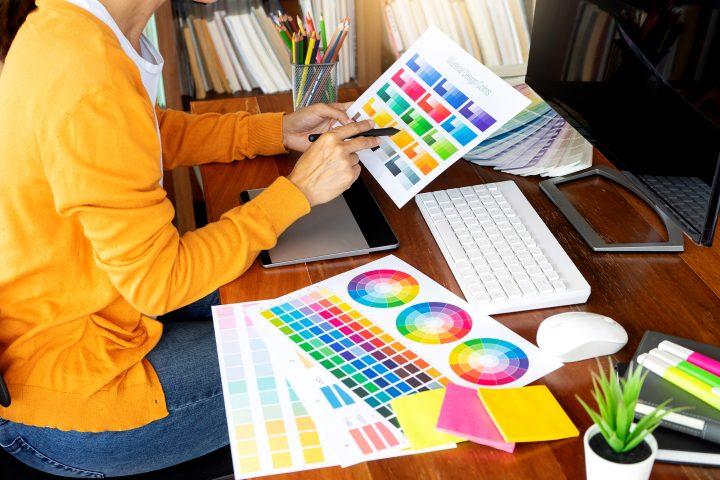 Uma profissional de design gráfico analisa palesta de cores sob uma mesa