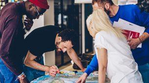 Três homens e uma mulher observam um mapa sob uma mesa