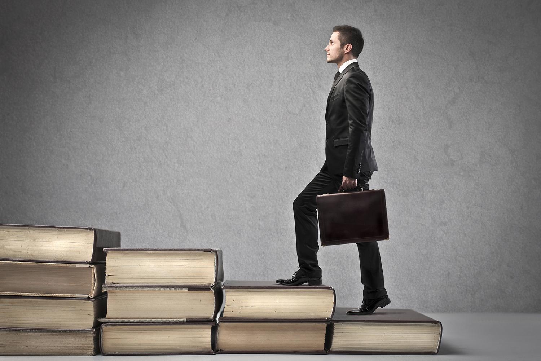 Empregabilidade-Homem de terno preto e pasta na mão subindo escada de livros