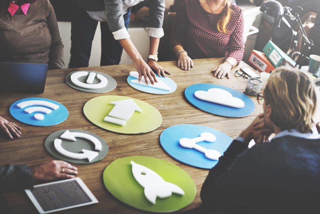 Profissionais de comunicação em uma mesa de reunião discutindo estratégias de mídias sociais