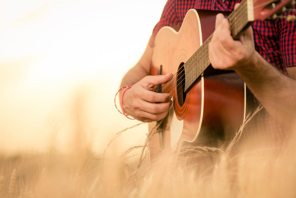 Homem segurando um violão e tocando o instrumento musical