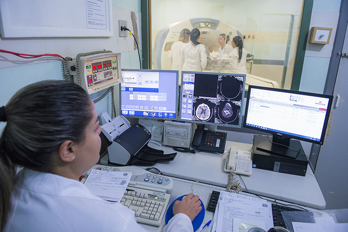 Profissional de radiologia em frente ao computador operando máquina de raio x