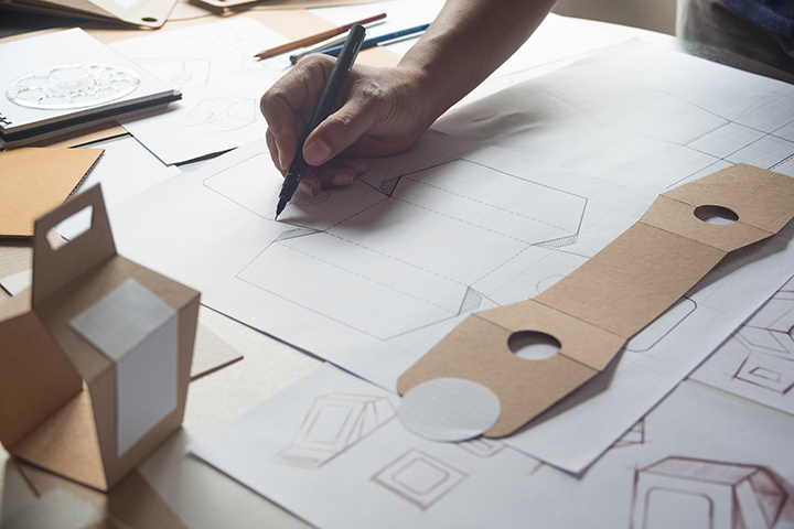 Imagem mostra uma das atividades de Design de Produto, com uma mão segurando uma caneta sobre alguns papéis com desenhos e anotações; ao lado o molde de uma caixa desmontada e outra montada