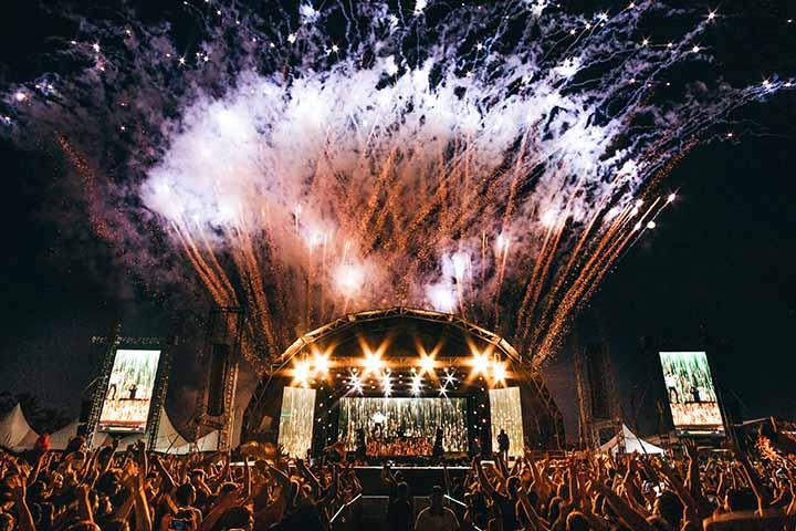 Produção cultural realiza shows com fogos de artificio ao fundo e a sombra de pessoas na plateia
