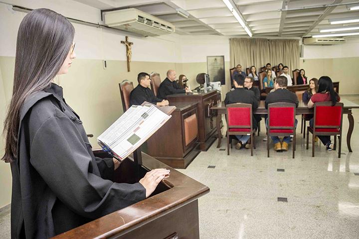 Estrutura de excelência do direito no tribunal do júri com menina em primeiro plano e demais pessoas no segundo