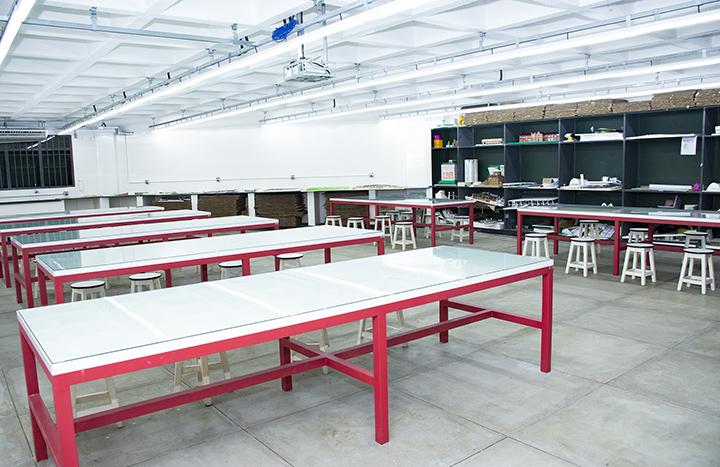 Sala grande com mesas e ao fundo uma prateleira e bancada para o desenvolvimento de trabalhos acadêmicos
