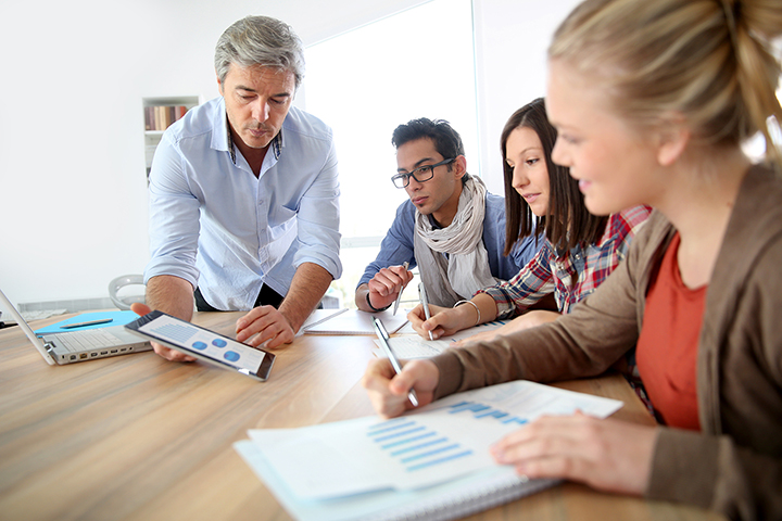 Grupo de pessoas em uma mesa com celular, computador e anotações trabalhando empreendedorismo