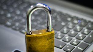 Golpe ilustrado com cadeado dourado com o feixe de ferro em cima de um teclado de computador