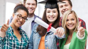 Nota do Enem abre portas com estudante segurando o diploma e amigos ao lado fazendo o sinal de joia