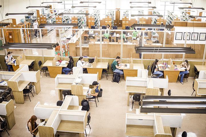 Foto área da biblioteca utilizada pela Faculdade de Informática com vários alunos estudando