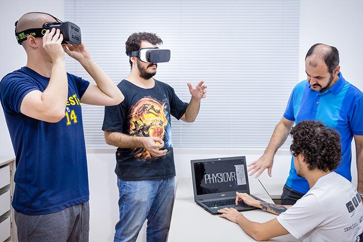 Três alunos fazem atividade com óculos 3D e professor orienta a atividade