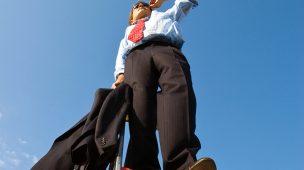 Homem de terno observando o céu de cima de uma escada, representando sucesso na carreira