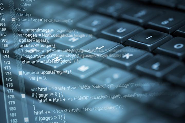 Um teclado de computador com uma imagem em marca d'água sobreposta, que mostra a tela de um computador com códigos de algum sistema sendo desenvolvido, representando a área da informática