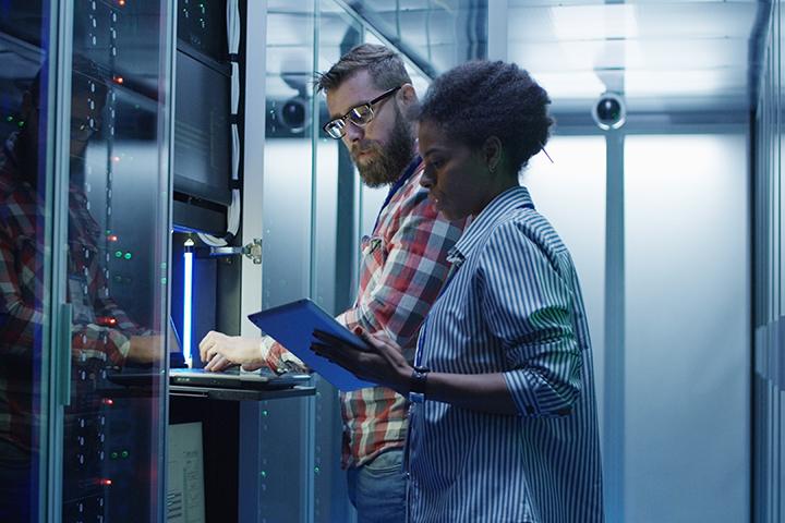 Homem e mulher profissionais da Gestão da TI trabalham no servidor de uma empresa