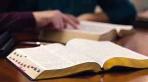 Teologia - Imagem dos braços e mãos de um homem e uma mulher sentados lendo a bíblia