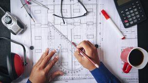 Arquitetura e engenharia: Mãos com um esquadro e um lápis desenhando sobre uma planta de construção, ao redor alguns objetos como calculadora, fone de isolamento acústico, compasso, óculos, entre outros