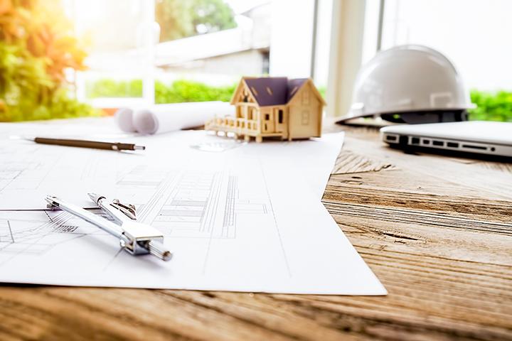 Construção civil aquecida: mesa com projeto, casa em miniatura e materiais
