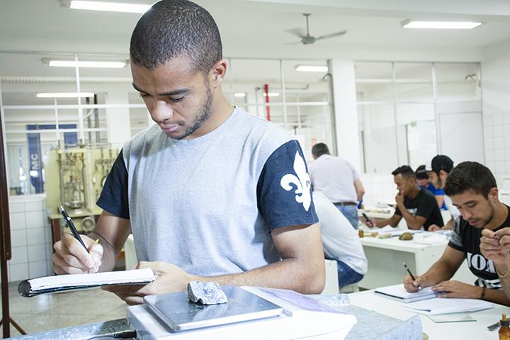 Estrutura top no laboratório de solos com aluno em pé segurando caderno