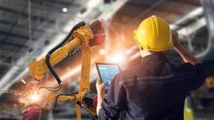 Profissional da engenharia numa indústria controlando uma máquina robô por meio de tablet na mão, representando a Indústria 4.0