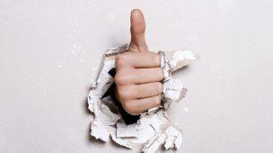 Engenharias: uma mão atravessando uma parede e acenando com o dedo polegar