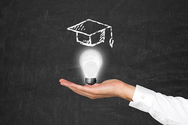 Faculdade EAD, presencial, semipresencial ou flexível: Uma mão segurando uma lâmpada e ao fundo um quadro verde com desenho de um capelo em cima da lâmpada