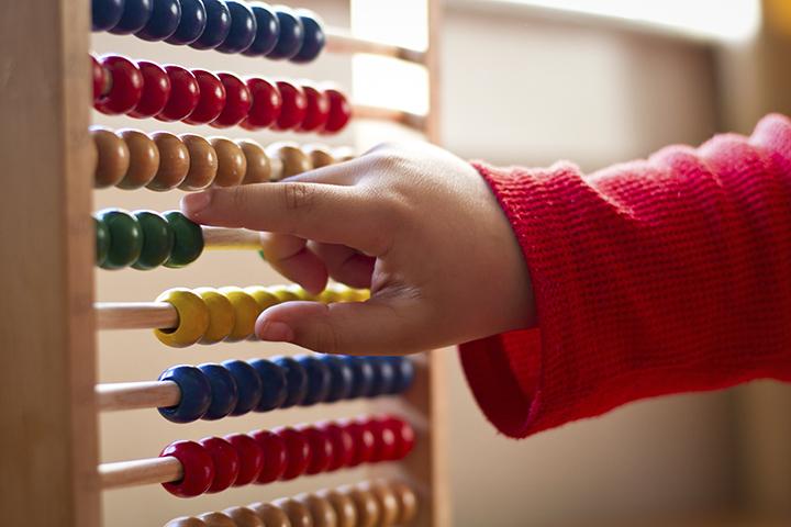 Jogos para educação: uma mão de criança manuseando um àbaco, instrumento que auxilia na aprendizagem das contas