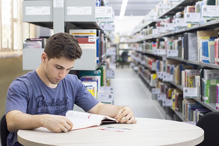 Professor aprende na biblioteca: menino lendo livro em uma mesa