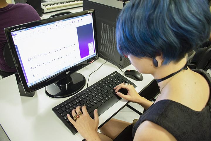 Professor: aluna em frente ao computador em aula de música