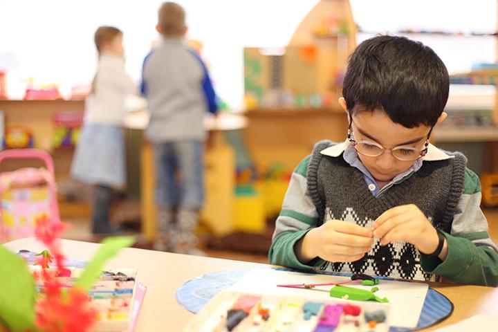Menino usando óculos de grau realiza atividade em mesa escolar, representando educação e tecnologia assistiva
