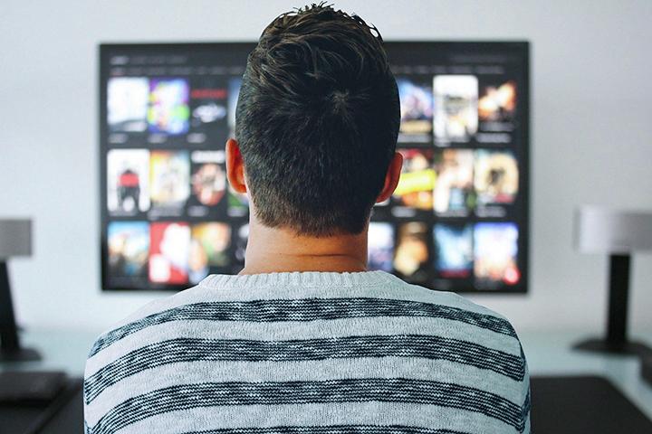 Filmes e séries Medicina: rapaz de costas com uma blusa listrada sentado em um sofá olhando para a TV que está ligada com a imagem desfocada