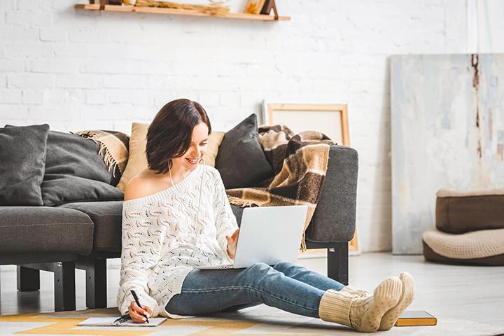 Estudar em casa: moça sentada com fone, caderno e notebook fazendo aula EAD