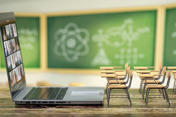 Faculdade mais barata: imagem mostra uma sala de aula vazia, com um notebook em cima da mesa e ao fundo carteiras e lousa