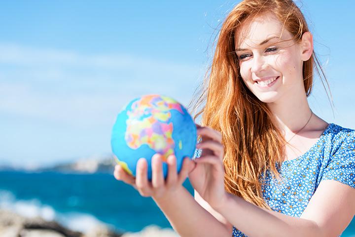 Estudar no exterior: jovem de cabelos longos e pele clara segurando e olhando um globo terrestre